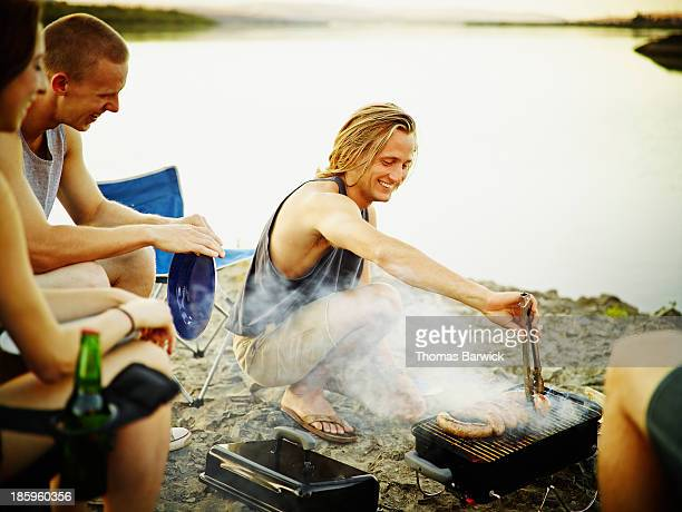 Man barbecuing for friends along river bank