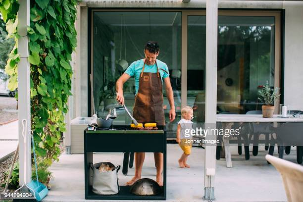 man barbecuing in garden - schürze stock-fotos und bilder