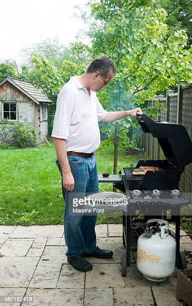 Man barbecuing in his backyard