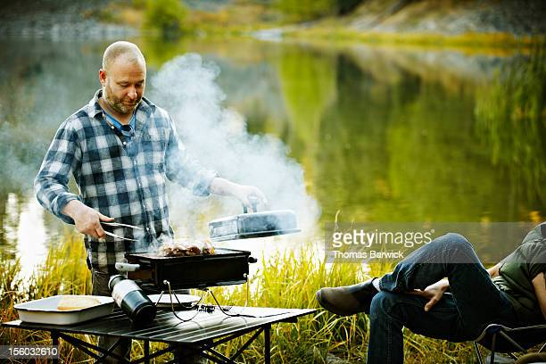 man barbecuing on grill near mountain lake - metal grate stock pictures, royalty-free photos & images