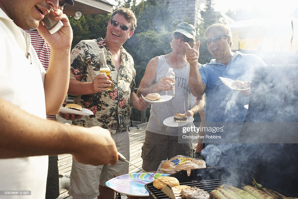 Man barbecuing using mobile phone, friends laughing in background : Stock Photo