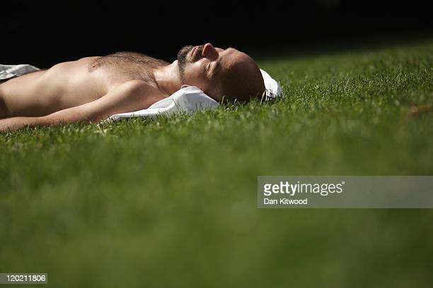 A man basks in the sunshine in Victoria Gardens on August 1 2011 in London England Temperatures in the capital reached around 27 degress today and...
