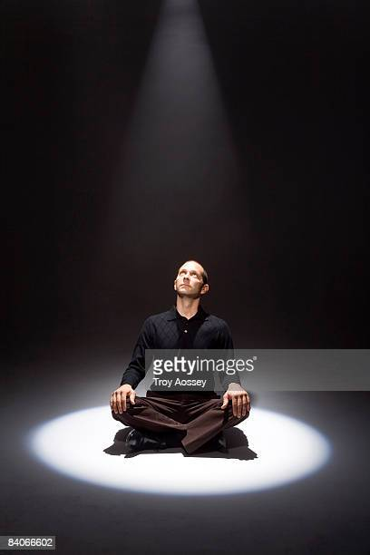 man bathed in shaft of light looking up
