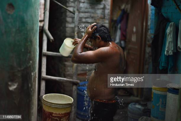 Man bathes at Sanjay Colony in Okhla Phase II, on June 12, 2019 in New Delhi, India. The city has been facing acute water shortage ever since the...