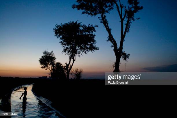 A man bathes in a canal as the sunsets June 16 2009 in Chota Lahore relief camp in Swabi Pakistan Over threemillion internally displaced persons are...