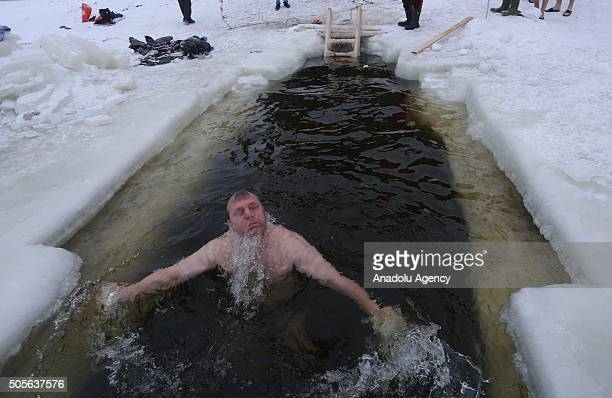 A man bathes in a river during Epiphany celebrations in Saint Petersburg Russia on 19 January 2015