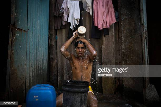 A man bathes in the Dharavi slum area of Mumbai India on Friday Nov 9 2012 Indian industrial production unexpectedly fell in September and the trade...