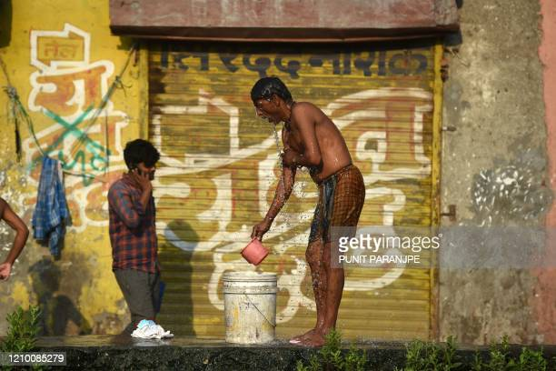 TOPSHOT A man bathes in the Dharavi slum during a governmentimposed nationwide lockdown as a preventive measure against the COVID19 coronavirus in...