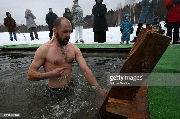 A man bathes in the icy cold water while celebrating the Epiphany church holiday in the village Kholmy on January 19 50 km west of Moscow Russia The...