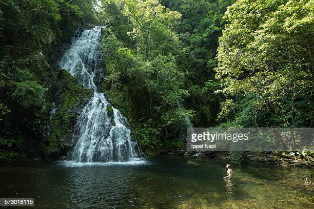 Man bathing in waterfall in lush forest