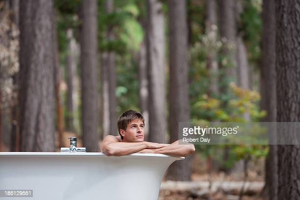 A man bathing outdoors in the woods