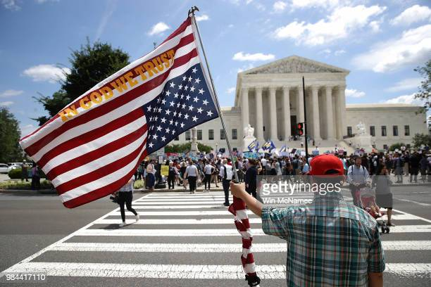 A man bearing an upside down American flag watches as protesters gather outside the US Supreme Court as the court issued an immigration ruling June...
