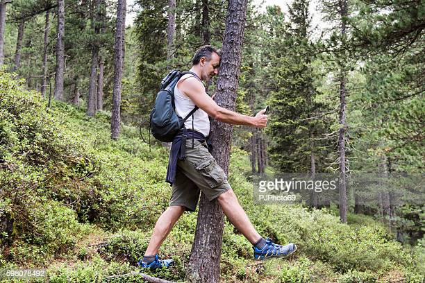 man beats against tree playing pokemongo on his smart phone - nederlaag stockfoto's en -beelden