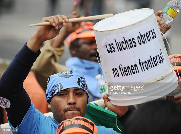 A man beats on a barrel with a sign that says The workers fight has no borders as he joins protesters at a rally of immigrant labor and faith...