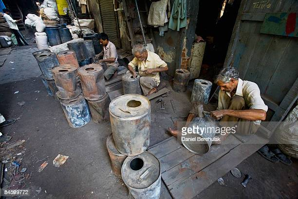 A man beats out dents out of empty cans as part of the recycling process in the Dharavi slum on February 3 2009 in Mumbai India The redevelopment of...