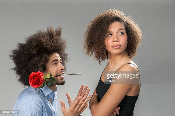man begging woman for forgiveness, holding a rose