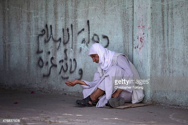 A man begs fo small change on the street on June 12 Gaza City Gaza The devastation across Gaza can still be seen nearly one year on from the 2014...