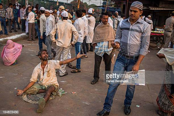 A man begs for alms as Indian Muslims gather for Eid alAdha prayers near Jama Masjid on October 27 2012 in New Delhi India Eid alAdha also known as...