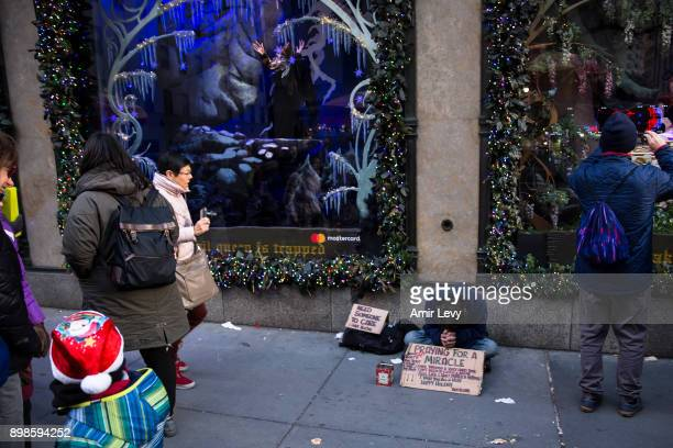 A man begs for money and help near a store decoration on Fifth Avenue on Christmas day on December 25 2017 in New York CitySecurity in New York is on...