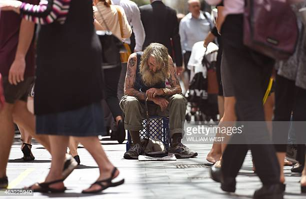 A man begs for money in Sydney's central business district as Australia's unemployment rate jumped to a morethan 12year high of 64 percent in January...