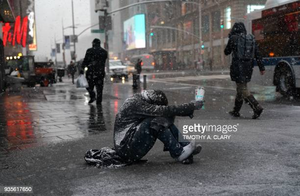 TOPSHOT A man begs for money in the snow along 42nd Street in Times Square in New York on March 21 as the fourth nor'easter in a month hits the...