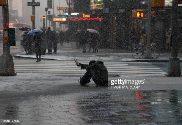 A man begs for money in the snow along 42nd Street in Times Square in New York on March 21 as the fourth nor'easter in a month hits the tristate area...