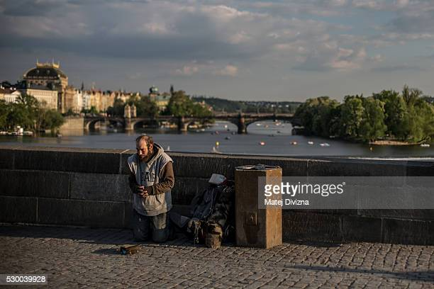 A man begs for money on the Charles Bridge on May 9 2016 in Prague Czech Republic The Charles Bridge construction began in 1357 by Charles IV's...