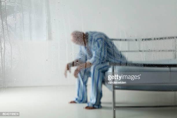 homme derrière une vitre de pluie - chambre hopital photos et images de collection
