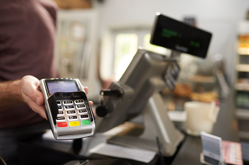 Man behind counter at a cafe offering credit card terminal 544446488