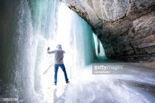 man behind frozen waterfall in minneapolis - behind waterfall stock pictures, royalty-free photos & images