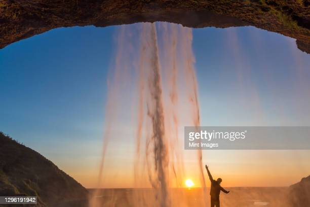 man behind seljalandsfoss waterfall, south iceland, iceland - flowing stock pictures, royalty-free photos & images