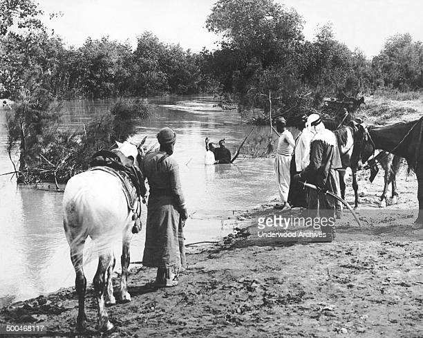 A man being baptized in a river in Jordan while other Arabs wait on the banks of the river Jordan circa 1926