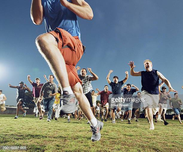 man being chased by crowd of yelling men - rushing the field stock pictures, royalty-free photos & images