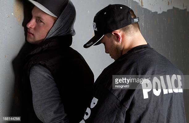 man being handcuffed by a policeman against a gray wall - arrest stock pictures, royalty-free photos & images