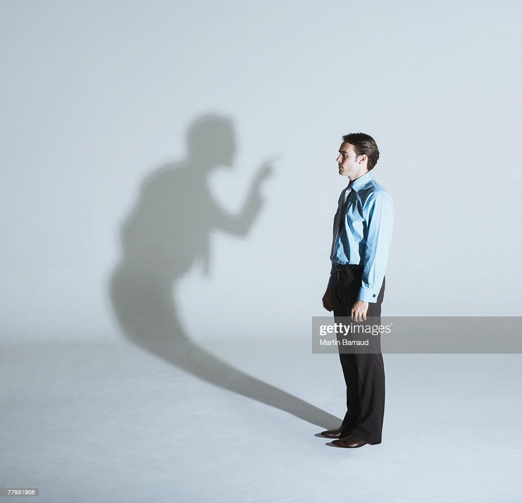 Man being scolded by his shadow : Stock Photo
