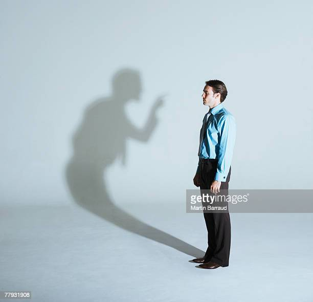 man being scolded by his shadow - illusion stock pictures, royalty-free photos & images