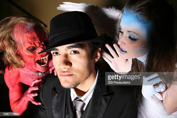 man being tempted by a devil and an angel - male angel stock photos and pictures