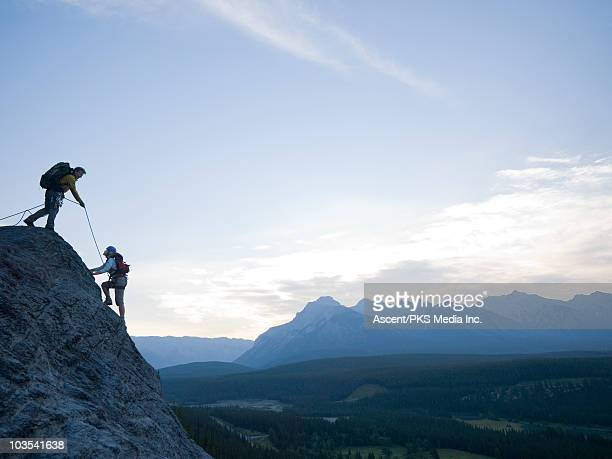 man belays woman to top of cliff above mtn valley - rock climbing stock pictures, royalty-free photos & images