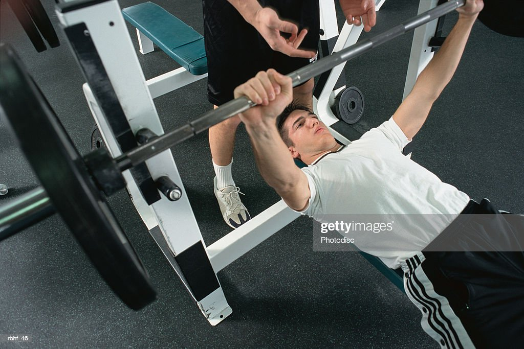 Man Bench Pressing Weights In A Gym With A Spotter : Stock Photo