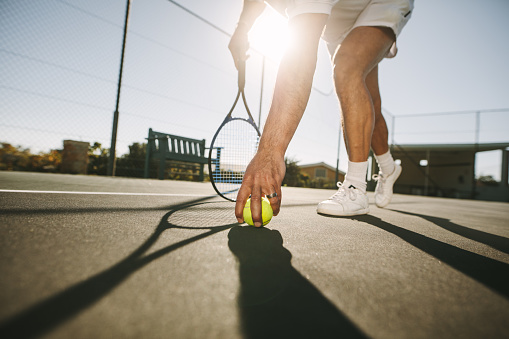 Man bending down to pick a tennis ball 1136388546