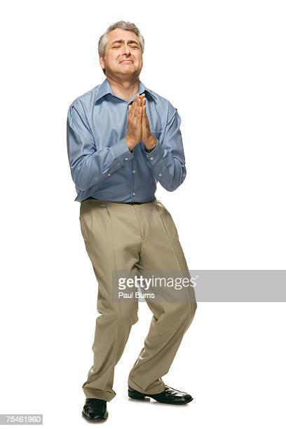 man bending on his knees and praying - suplicar imagens e fotografias de stock
