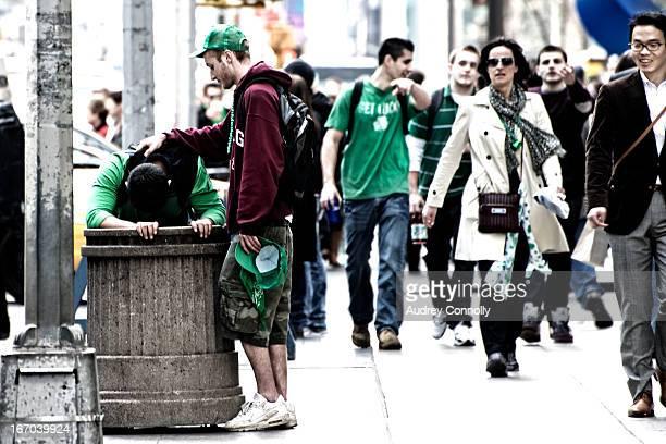 Man bent over trashcan sick, ten o'clock in the morning, annual Saint Patrick's Day Parade, Midtown Manhattan, New York City