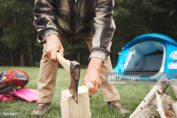 Man beside tent, using axe to chop firewood, mid section