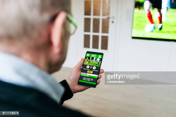 man bets on soccer game with betting app on phone at home - gambling stock pictures, royalty-free photos & images