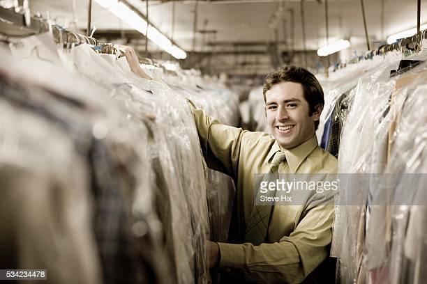 Man Between Racks of Dry Cleaning