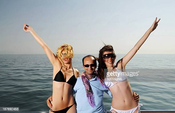 Man between two beautiful girls on the yacht