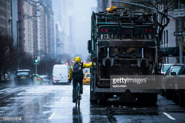 man bicycling in manhattan holding on to garbage truck - garbage truck stock pictures, royalty-free photos & images