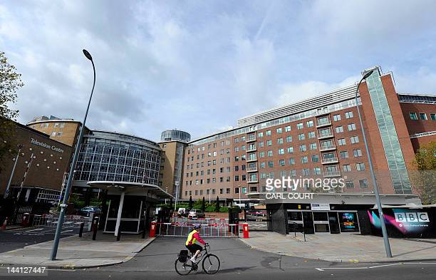 A man bicylces past one of the entrances to the BBC Television Centre offices in west London on October 6 2011 The British Broadcasting Corporation...