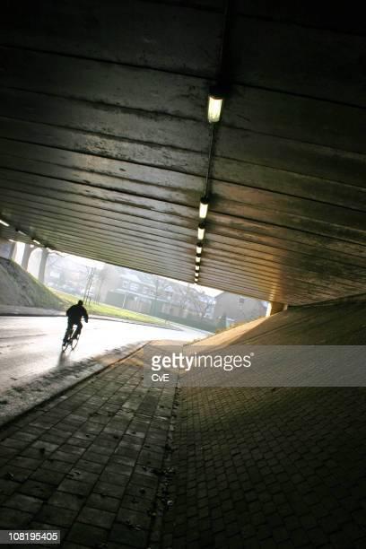 Man Bicyling Under Tunnel