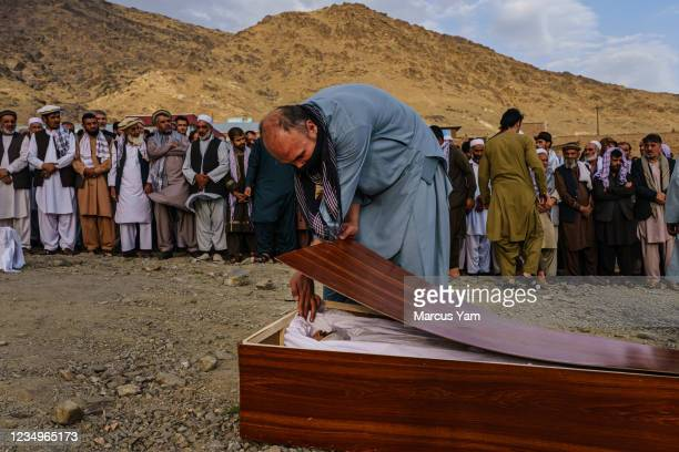 Man bids a respectful farewell to Zemari Ahmadi in his casket during a mass funeral for members of a family - that is said to have been killed in a...